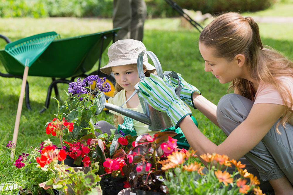 Photo of Mother and Daughter Watering Garden Flowers